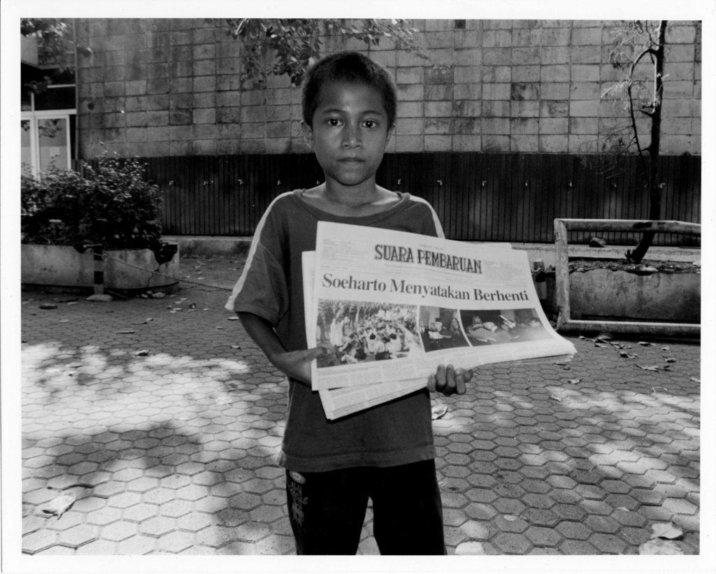 インドネシア人の少年が新聞の束を持って、その一面をカメラに向けている