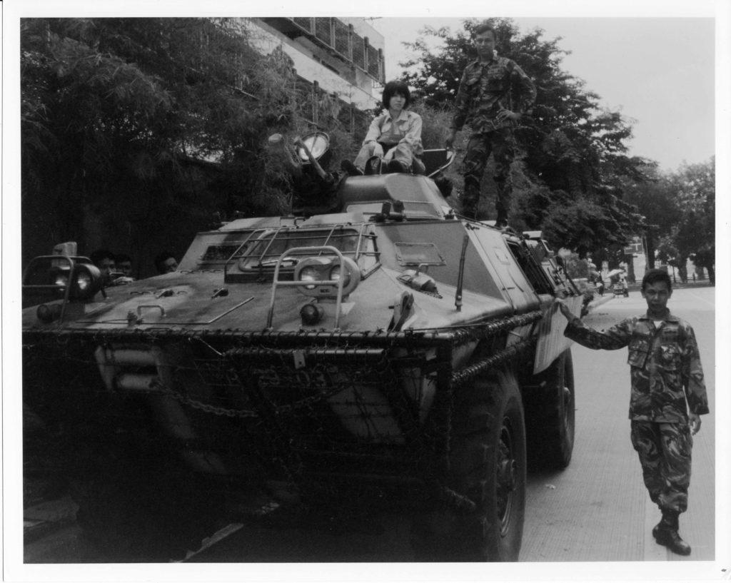 道端で待機・警戒する装甲車に乗せてもらった筆者。インドネシア軍兵士が傍らに立っている